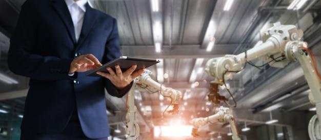 Gerente ingeniero industrial que usa la máquina de brazos robotizados de control y control de tabletas