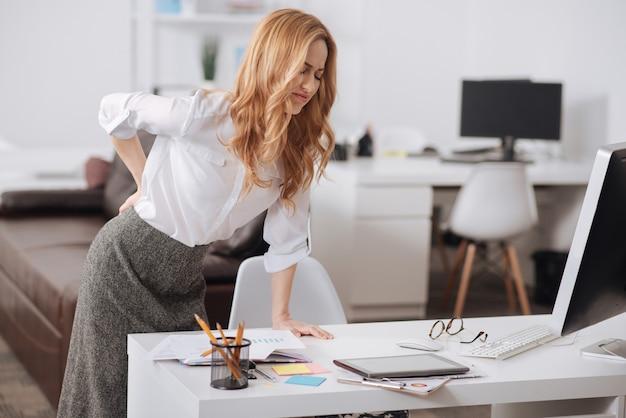 Gerente joven calificado molesto de pie en la oficina y trabajando mientras toca su espalda y sufre de dolor