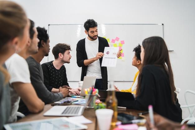 Gerente liderando una reunión de lluvia de ideas.