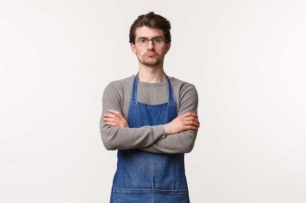 Gerente masculino escéptico de aspecto serio que mira a los empleados que miran cómo trabajan, gruñón mirando con las manos cruzadas sobre el pecho, decepcionado o reacio, parado en un delantal en la cafetería