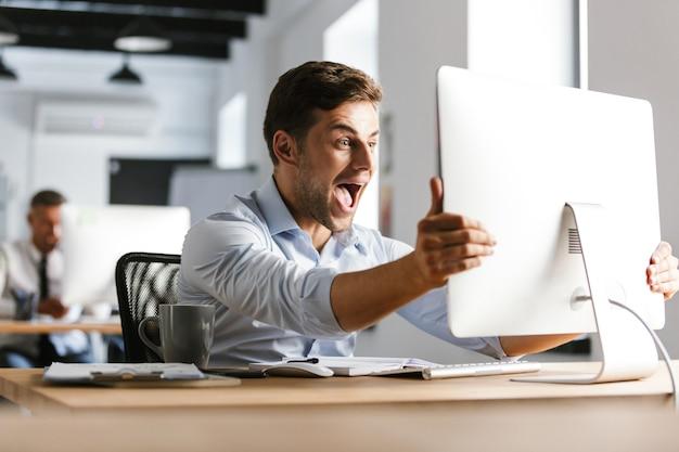 Gerente masculino feliz sorprendido gritando y regocija