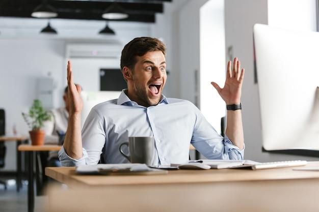 Gerente masculino feliz sorprendido se regocija mientras usa la computadora