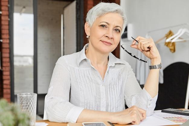Gerente de moda elegante madura de 50 años con cabello gris de duendecillo sosteniendo gafas y con una sonrisa segura, revisando documentos financieros, haciendo trámites con calculadora