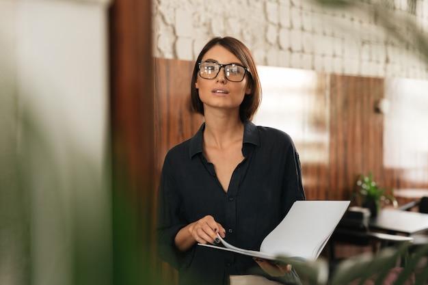 Gerente de mujer en anteojos con documentos en manos