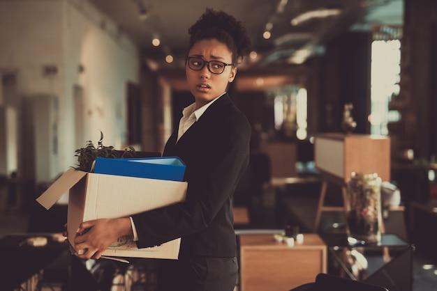 Gerente de mujer deja lugar de trabajo con caja de oficina.