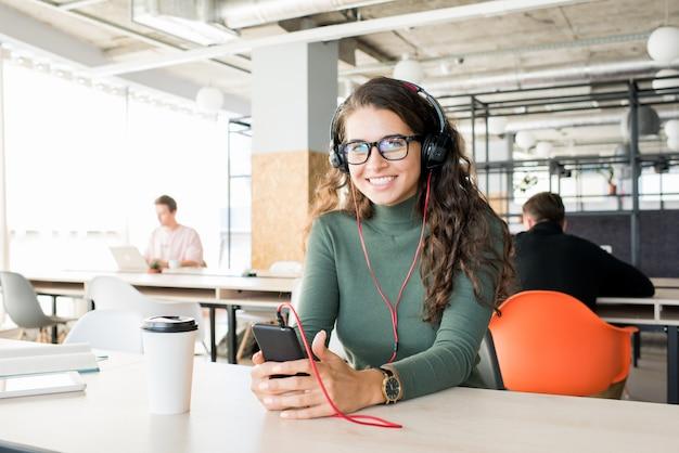 Gerente mujer emocionada escuchando música en el lugar de trabajo