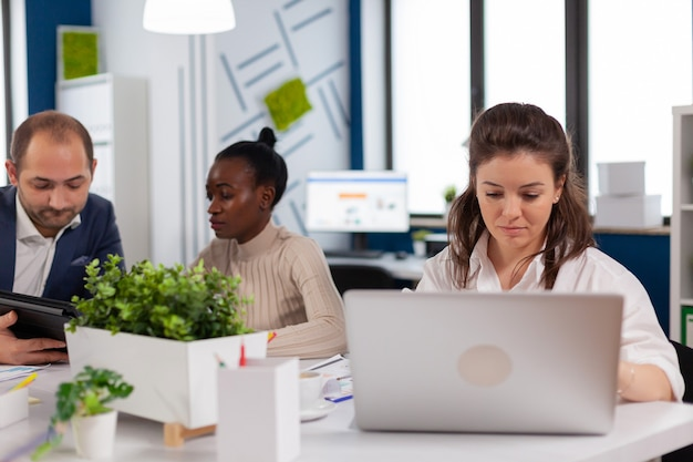 Gerente de mujer enfocada escribiendo en la computadora portátil, navegando en internet mientras está sentado en el escritorio concentrado con múltiples tareas