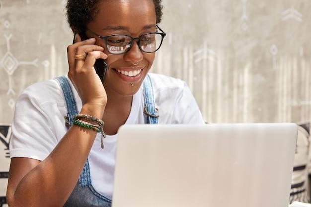 Gerente de mujer joven alegre exitosa llama a través de un teléfono inteligente mientras trabaja en una computadora portátil
