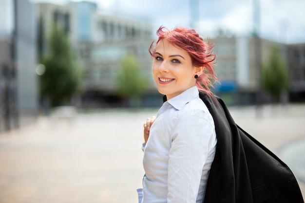Gerente de mujer joven confidente al aire libre en un entorno urbano moderno