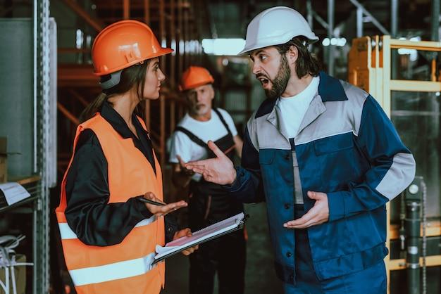 Gerente mujer joven discutiendo con trabajador de almacén