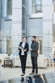 Gerente de mujer joven sonriente en traje negro que muestra datos estadísticos en el portapapeles a un colega en el pasillo de la oficina