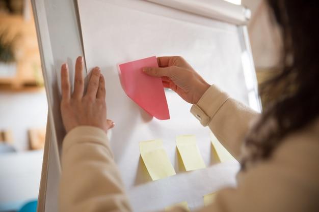 Gerente de mujer pegando notas de papel en blanco en el rotafolio