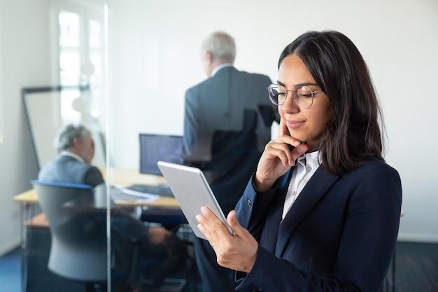 Gerente de mujer pensativa en gafas mirando en la pantalla de la tableta y sonriendo mientras dos empresarios maduros discutiendo el trabajo detrás de la pared de vidrio. copie el espacio. concepto de comunicación