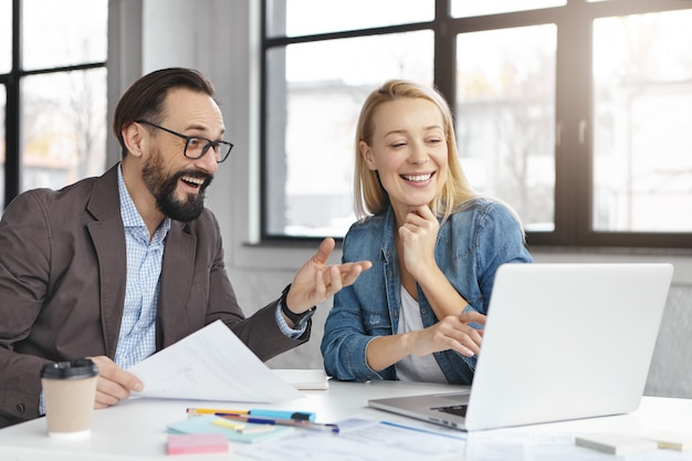 Gerente mujer rubia feliz tiene conversación con colega masculino