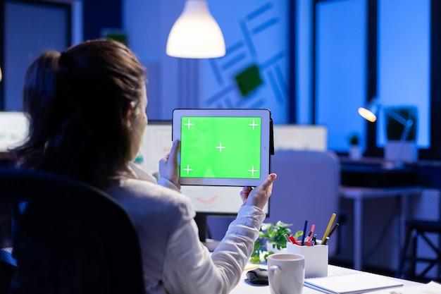 Gerente mujer sosteniendo tableta con monitor de pantalla verde durante la conferencia web en línea