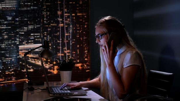 Gerente de mujer trabajando en la computadora y hablando.