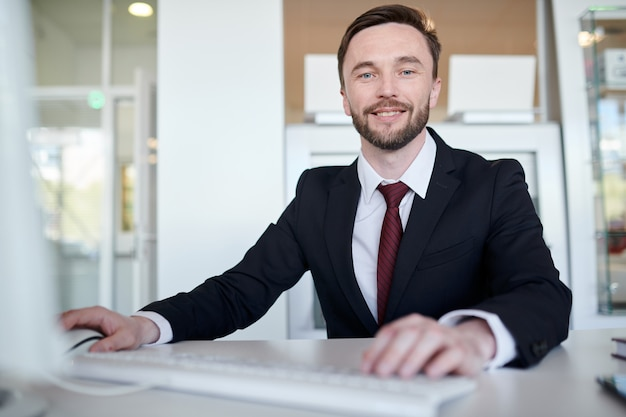 Gerente de negocios guapo en el escritorio