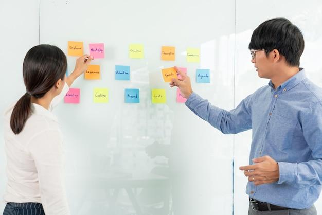 Gerente de negocios que muestra una idea para su equipo y pega muchos papeles de notas en la ventana de vidrio para trabajar con éxito en la oficina creativa de reuniones de negocios, concepto de planificación y gestión.