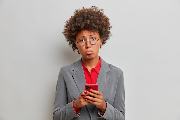 La gerente o asistente ejecutiva triste y decepcionada tiene problemas en el trabajo, usa el teléfono móvil, espera una llamada importante, no puede resolver una situación difícil, permanece en el interior. tecnología