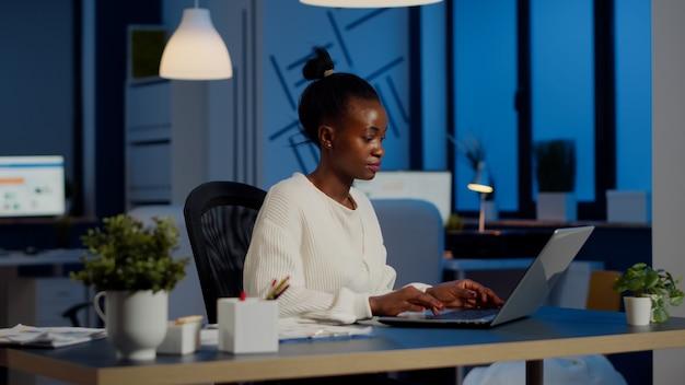 Gerente ocupado trabajando en informes financieros verificando gráficos de estadísticas, escribiendo en la computadora portátil sentado en el escritorio a altas horas de la noche en la oficina de puesta en marcha haciendo horas extras para respetar la fecha límite del proyecto financiero