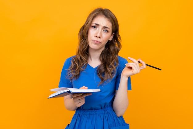 Gerente de oficina con un cuaderno y un lápiz en las manos sobre un fondo de una pared amarilla
