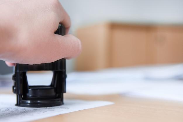 Gerente pone un sello en el documento en la oficina