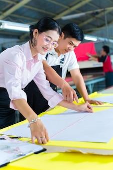 Gerente de producción y diseñador asiático en fábrica