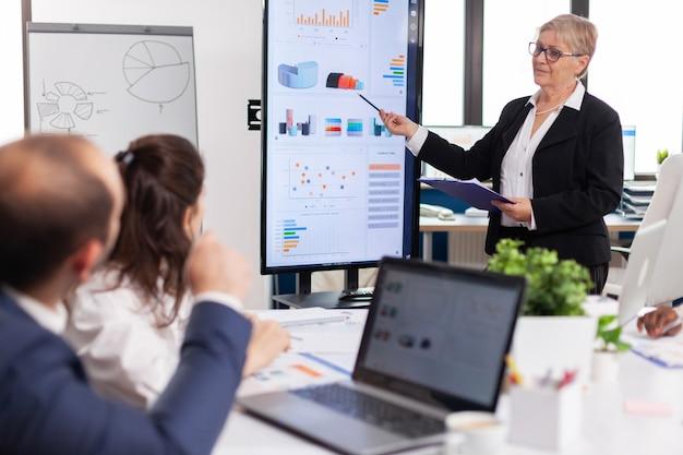 Gerente de proyecto anciano apuntando al escritorio presentando datos estadísticos, informando a un grupo diverso de empleados