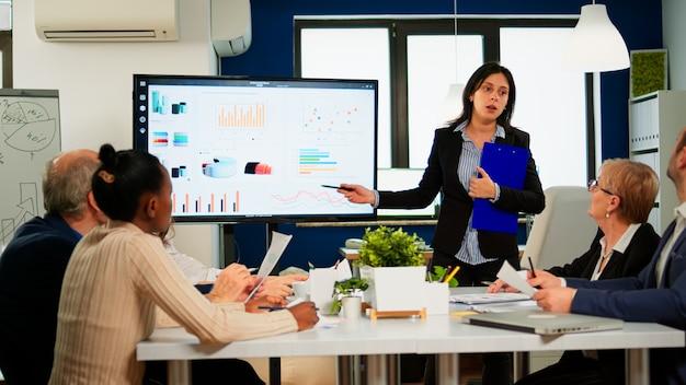 Gerente de proyecto femenino que lleva a cabo una reunión financiera que muestra gráficos estadísticos y tablas en el dispositivo de pantalla táctil de pizarra interactiva. director ejecutivo que trabaja en la amplia sala de la agencia creativa.