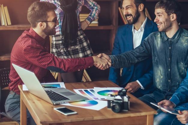 Gerente de publicidad con un apretón de manos saluda al cliente