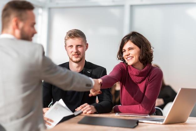 Gerente de recursos humanos un apretón de manos con joven solicitante de empleo