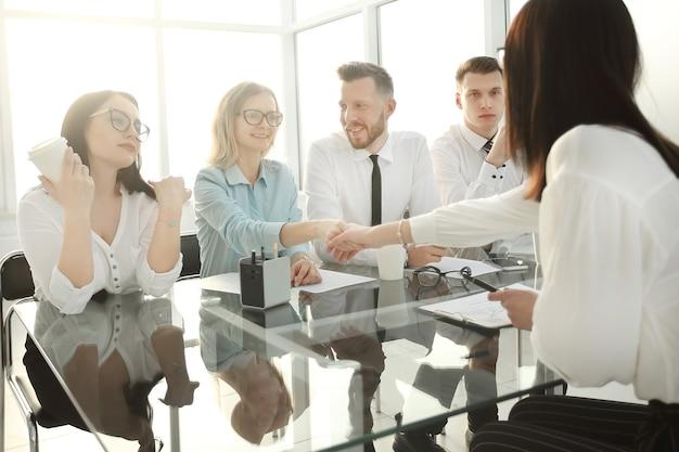 El gerente de recursos humanos le da la mano al candidato para el puesto vacante. el concepto del casting empresarial