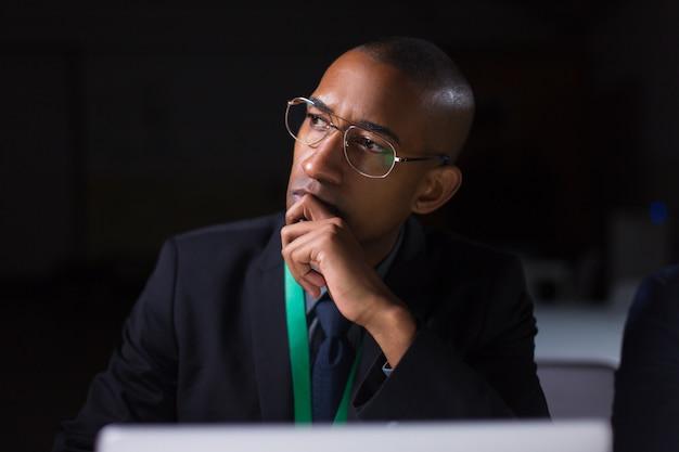 Gerente reflexivo trabajando en la oficina a altas horas de la noche