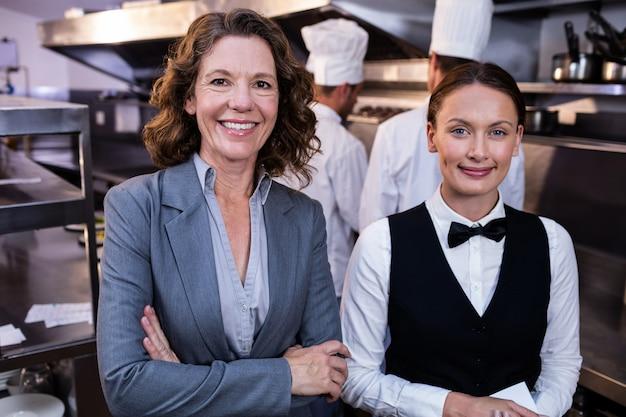 Gerente de restaurante y camarera sonriendo en cocina comercial
