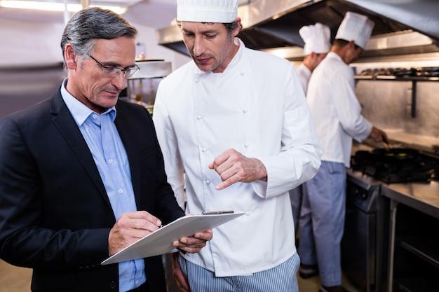 Gerente de restaurante masculino escribiendo en el portapapeles mientras interactúa con el jefe de cocina