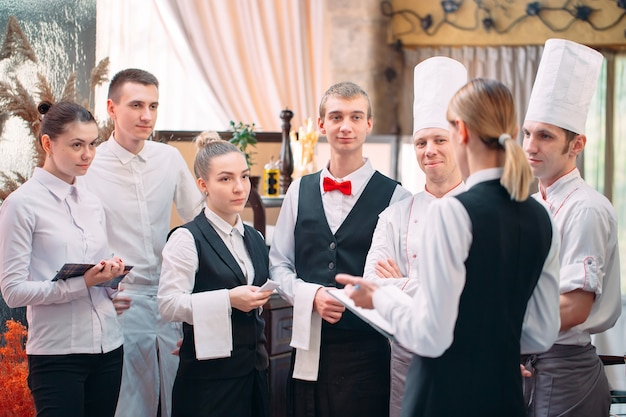 El gerente del restaurante y su personal en la cocina. interactuando con el jefe de cocina en la cocina comercial.