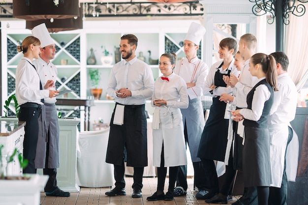 El gerente del restaurante y su personal en la terraza. interactuando con el jefe de cocina en el restaurante.