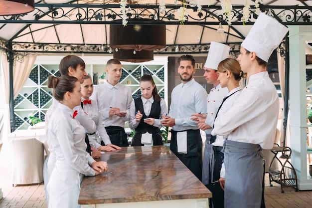 El gerente del restaurante y su personal en la terraza, interactuando con el jefe de cocina en el restaurante,