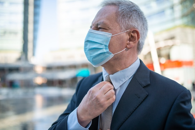 Gerente senior ajustándose la corbata mientras camina al aire libre con una máscara durante el coronavirus y la pandemia de covid