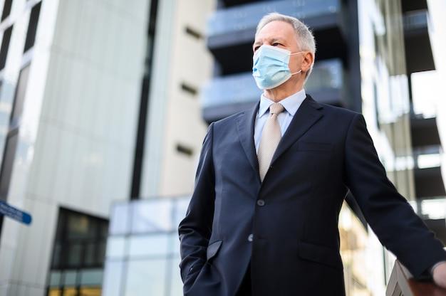 Gerente senior con los brazos cruzados con una máscara protectora al aire libre contra covid 19