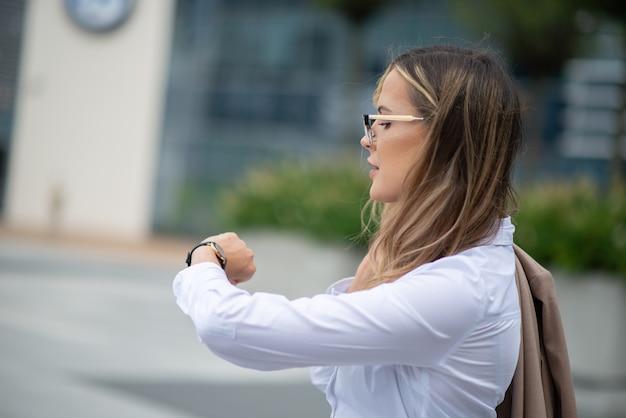 Gerente de sexo femenino joven confiado que controla la hora en su reloj al aire libre