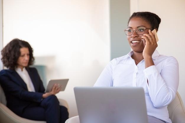 Gerente de sexo femenino joven positivo hablando por teléfono