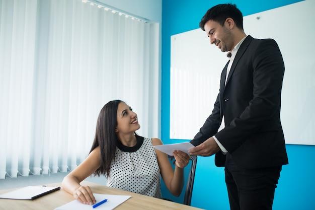 Gerente de sexo femenino joven sonriente que da el contrato al cliente masculino