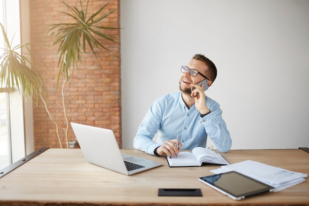 Gerente de sexo masculino alegre maduro que trabaja en la computadora portátil, anotando información en el cuaderno,