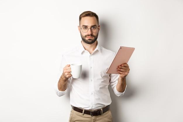 Gerente de sexo masculino confiado leyendo trabajo en tableta digital y tomando café, de pie sobre fondo blanco.