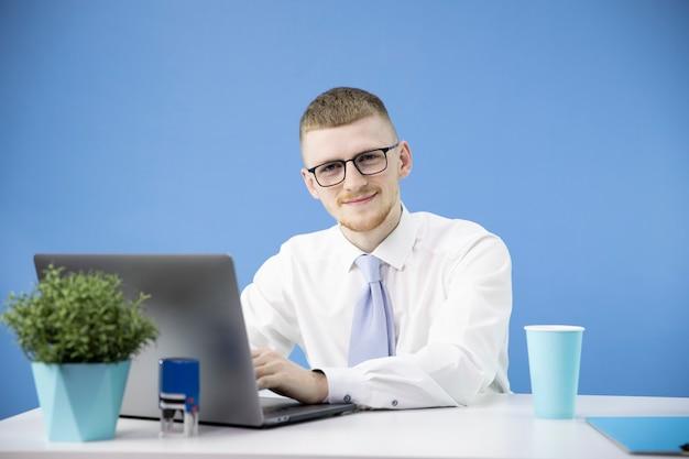 Gerente de sexo masculino en la oficina trabaja con laptop acento sonriente en azul