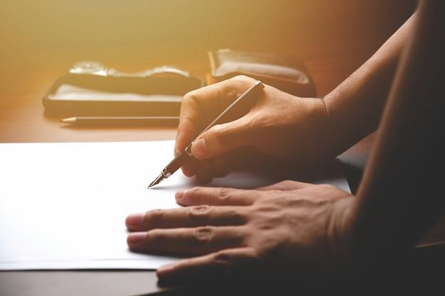 Gerente de sexo masculino poniendo sus ideas y escribir el plan de negocios en el lugar de trabajo. hombre sujetando lápiz haciendo notas en documentos en papel sobre la mesa en la oficina