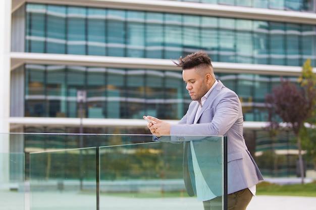 Gerente de sexo masculino serio que nota en smartphone