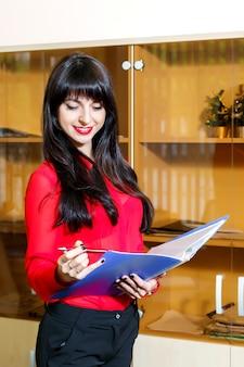 Gerente sonriente en una blusa roja con una carpeta de documentos en la oficina