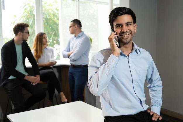 Gerente sonriente hablando por teléfono móvil